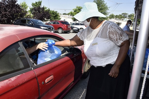 New Carrollton, Maryland, Mayor Mayor Phelecia E. Nembhard hands a bag of food to a motorist during a food giveaway outside Ebenezer Church of God in Hyattsville on June 5. (Robert R. Roberts/The Washington Informer)