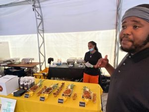 """Cleavon """"Clay"""" Morris, chef and owner of The Tropical Express, describes his dishes on display during the Flavors of the DMV Showcase hosted by the Washington Football Team at FedEx Field in Landover, Maryland, on June 14. (William J. Ford/The Washington Informer)"""