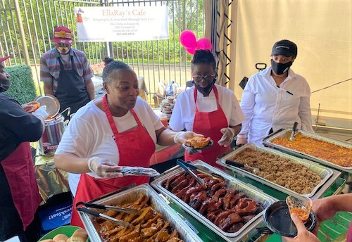 Ella Willis-Walters (center) helps serve samples of Southern-style cuisine from EllaRay's Café during the Flavors of the DMV Showcase hosted by the Washington Football Team at FedEx Field in Landover, Maryland, on June 14. (William J. Ford/The Washington Informer)