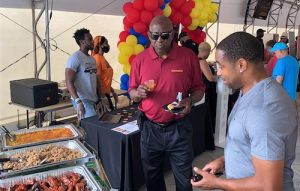 """Former Washington Football Team players Rick """"Doc"""" Walker (left) and Fred Smoot sample food at the Flavors of the DMV Showcase hosted by the team at FedEx Field in Landover, Maryland, on June 14. (William J. Ford/The Washington Informer)"""