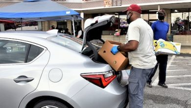 Members of Union Bethel AME Church in Temple Hills, Maryland, prepare to load food into a vehicle's trunk during a food distribution event on July 24. (Robert R. Roberts/The Washington Informer)