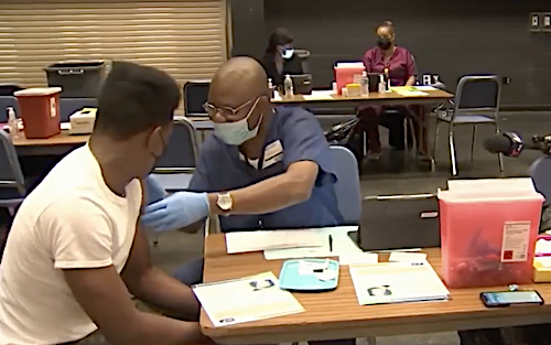 A youth receives a coronavirus vaccination at a mobile clinic held at Oxon Hill High School in Oxon Hill, Maryland, on July 14. (Screen shot courtesy of WRC-TV)