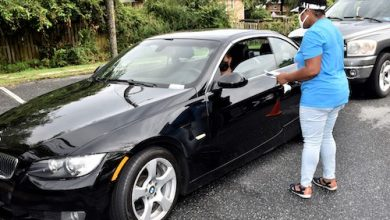 Prince George's County Executive candidate Tonya Sweat chats with a driver during an Aug. 17 food giveaway at St. Stephen Baptist Church in Temple Hills, Maryland. (Robert R. Roberts/The Washington Informer)