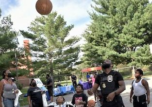"""**FILE** A District Heights police officer plays basketball during a """"Stop the Violence"""" event hosted by State's Attorney Aisha Braveboy on June 25. (Robert R. Roberts/The Washington Informer)"""