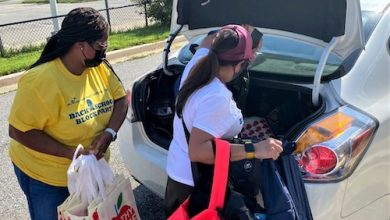 Prince George's County Public Schools employees Dr. Jennifer Love (left) and Maria Smith load backpacks and school supplies in the trunk of a car on Aug. 21. (William J. Ford/The Washington Informer)
