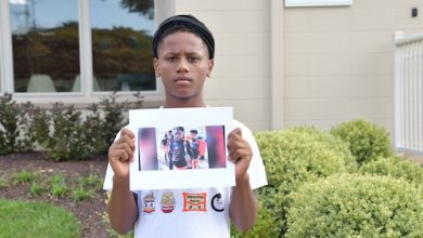 Jamal Gomez holds a photo of the late Davon McNeal. (Anthony Tighlman/The Washington Informer)