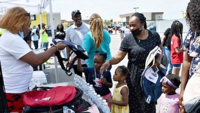 A girl receives a free backpack during an Aug. 14 event hosted by Del. Darryl Barnes at Ritchie Station in Capitol Heights, Maryland. (Anthony Tilghman/The Washington Informer)