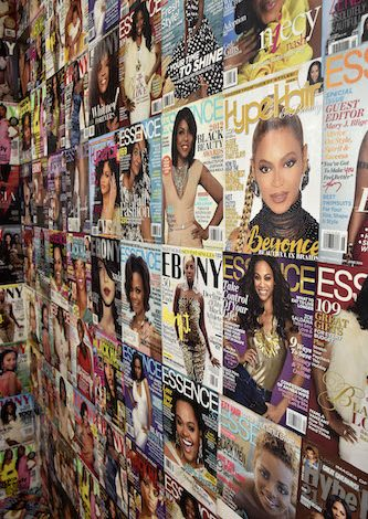 Magazine covers targeting Black women are spread on a wall at one of the installations at The Black Hair Experience, an exhibition at National Harbor in Oxon Hill, Md., running through the end of 2021. (Robert Roberts/The Washington Informer)