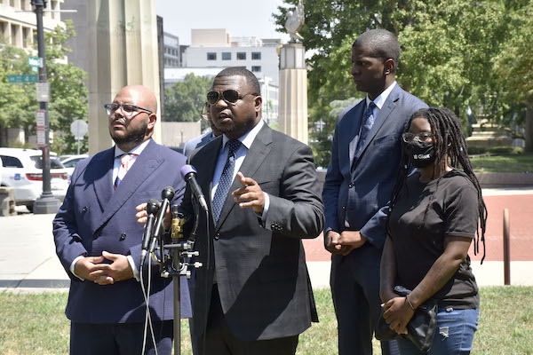 Attorneys for Kiman Johnson, a 23-year-old Black man punched in the face by a Metropolitan Police officer while restrained, join Johnson's twin sister Kimani (right) during an Aug. 13 press conference outside the police department headquarters in northwest D.C. addressing the attack. (Robert R. Roberts/The Washington Informer)