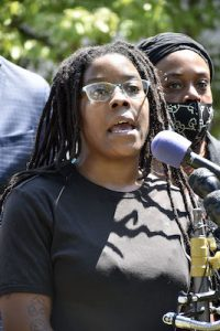 Kimani Johnson, twin sister of Kiman Johnson, a 23-year-old Black man punched in the face by a Metropolitan Police officer while restrained, speaks during an Aug. 13 press conference outside the police department headquarters in northwest D.C. addressing the attack. (Robert R. Roberts/The Washington Informer)