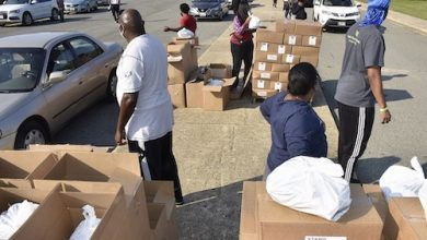 Volunteers prepare to put bags and boxes of food in vehicles at a Sept. 11 distribution giveaway by Kingdom Fellowship AME Church at High Point High School in Beltsville. (Robert R. Roberts/The Washington Informer)