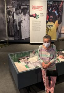 Vivian Williams stands in front of a case containing photographs and documents showcasing her community advocacy work. (Samir Meghelli/Smithsonian Anacostia Community Museum)