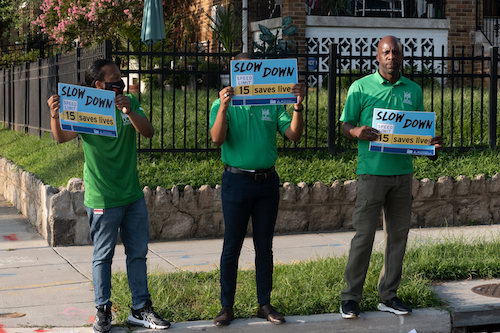 Volunteers stand on a corner holding up signs asking drivers to slow down to help students arrive at school safely. (Shevry Lassiter/The Washington Informer)