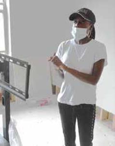 Homeowner Brittany Bennett surveys damage in her unit. (Roy Lewis/ The Washington Informer)