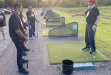 """Ray Savoy, Langston Golf Course instructor, gives everyone at the """"Clubs Not Guns"""" bi-weekly event, held throughout the month of August, a lesson on holding golf clubs. (Rob Warren/The Washington Informer)"""