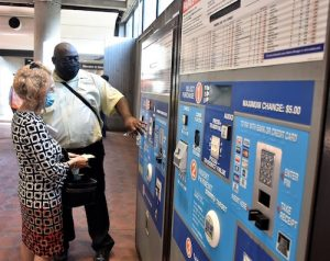 P.A. Hill, one of the two managers at the Prince George's Plaza Metro station in Hyattsville, Maryland, helps a rider at a fare vending machine. The Metro station was one of four in Prince George's County that reopened Sept. 7. (Robert R. Roberts/The Washington Informer)