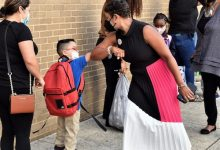 Prince George's County Public Schools CEO Monica Goldson greets a Deerfield Run Elementary student with an elbow bump on Sept. 8, the first day of school in the county. (Robert R. Roberts/The Washington Informer)