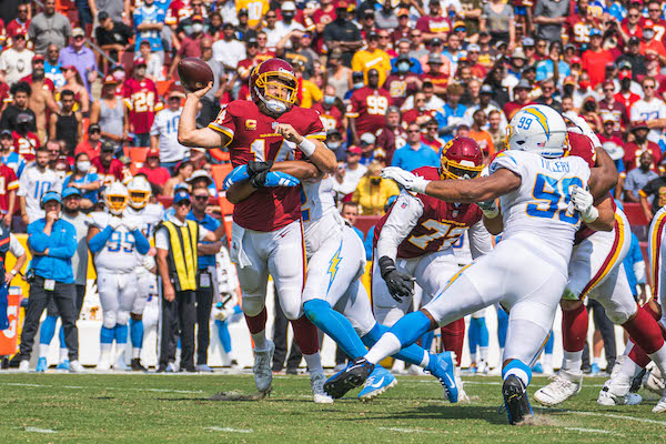 Washington Football Team quarterback Ryan Fitzpatrick is sacked during a 20-16 home loss to the Los Angeles Chargers at FedEx Field, in Landover, Md., on Sept. 12, 2021. (Abdullah Konte/The Washington Informer)