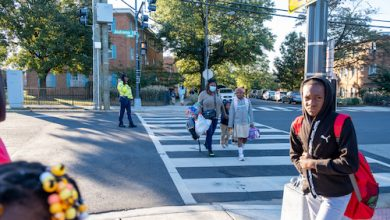 A crossing guard helps young people cross Alabama Avenue to enter nearby Turner Elementary School. (Ja'Mon Jackson/The Washington Informer)