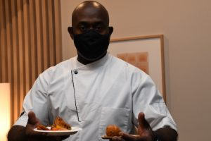 """Chef Willie from the Embassy of the Bahamas shows his Fred & Stilla menu items. Beginning in October, his fried snapper with spicy bell peppers, peas and rice and conch fritters will be served for the """"Global Table"""" theme at the restaurant located in The Ven at Embassy Row. (Anthony Tilghman/ The Washington Informer)"""