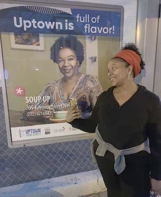 Donna Henry, owner of Soup Up in Northwest, admires an ad for her business. (WI photo)