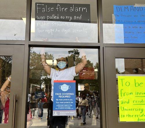 Howard University senior Aniyah Vines holds up a sign at the university's Blackburn Center during a student sit-in on Oct. 13. (Anthony Tilghman/The Washington Informer)