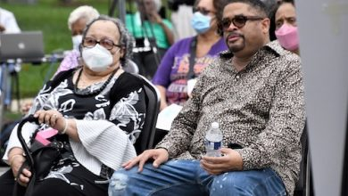 Gospel singer Byron Cage (right) sits besides his mother and a Cameron Grove resident at a community rally on Oct. 13. (Anthony Tilghman/The Washington Informer)